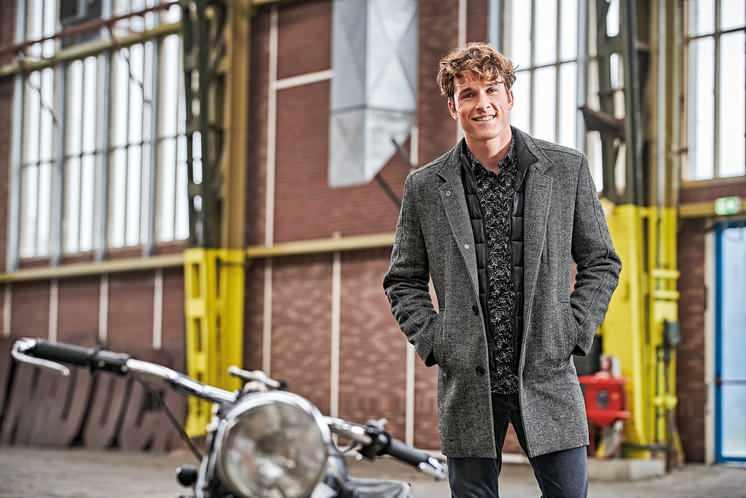 Model trägt Mantel und steht neben einem Motorrad