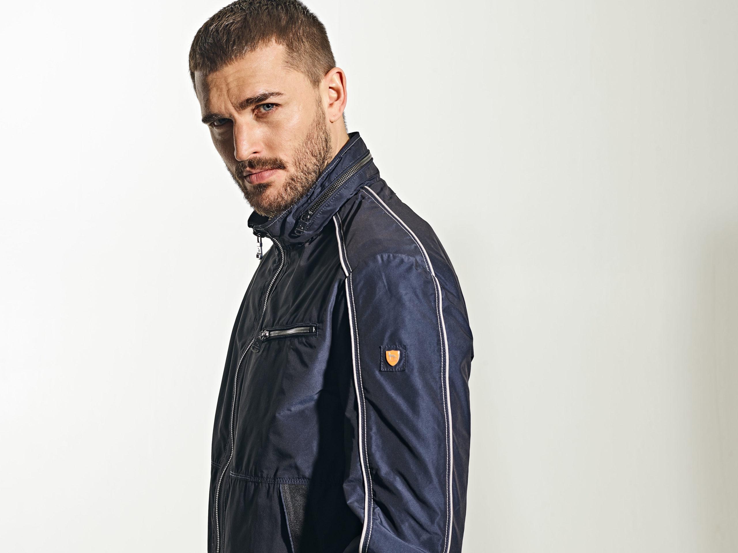 Mann in sportiver Jacke vor cleanem Hintergrund
