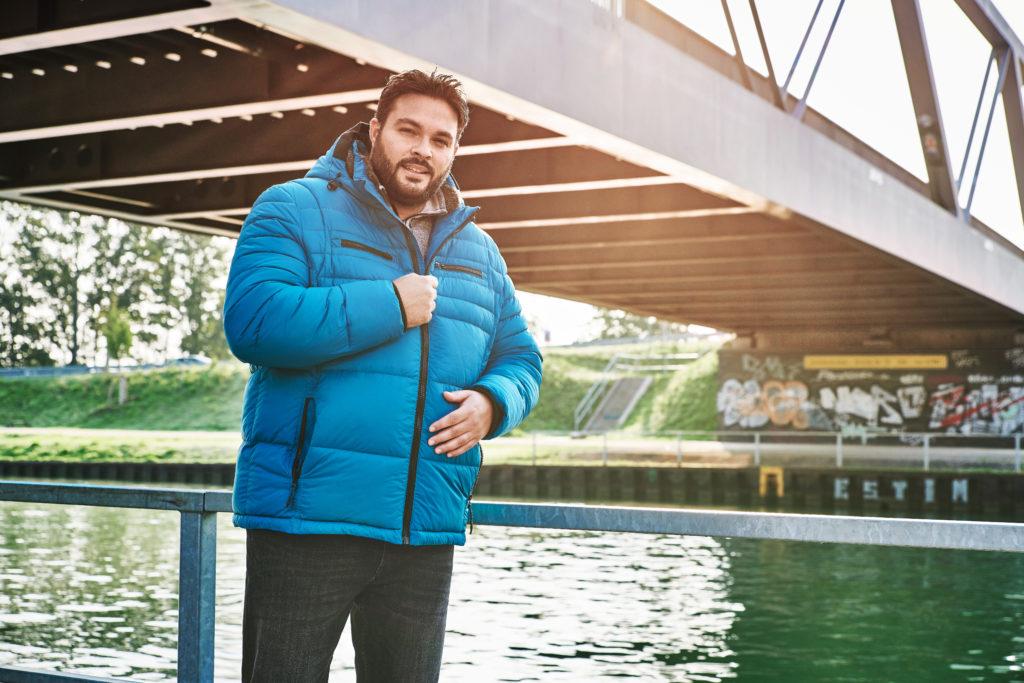 Plus Size Model steht neben einem Geländer am Kanal